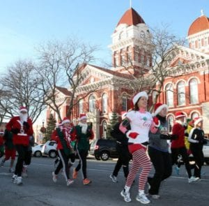 Participants run by the Courthouse at the Santa Run, Walk & Ride.