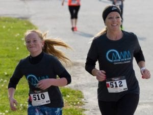 A Mom running with her daughter at the Run Like a Mother 5K.